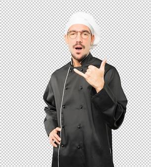 Verbaasd jonge chef-kok een gebaar maken van bellen met de hand