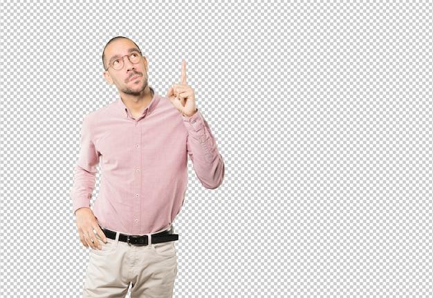 Verbaasd jonge man die met zijn vinger omhoog wijst