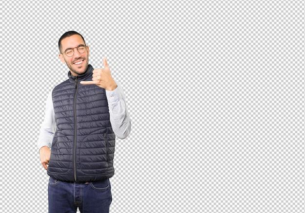 Verbaasde jonge man die een gebaar maakt om met de hand te bellen