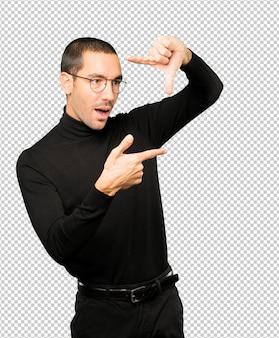 Verbaasde jonge man die een gebaar maakt van het nemen van een foto met de handen