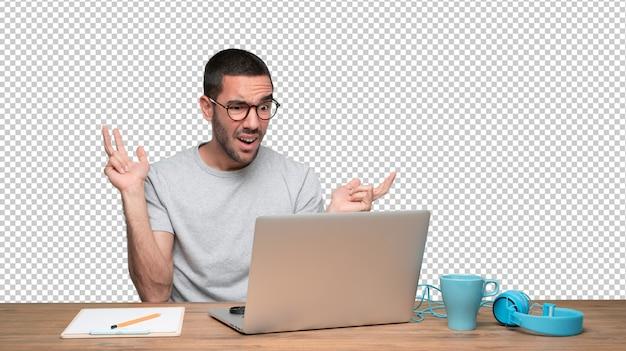 Verbaasde jonge man zit aan zijn bureau