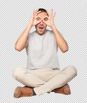 Verbaasde jongeman die zijn handen als een verrekijker gebruikt