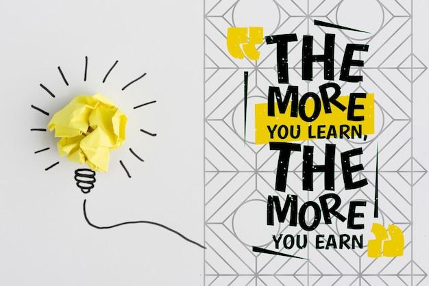 Verfrommeld papier in de vorm van een gloeilamp en hoe meer je leert, hoe meer je citaat verdient