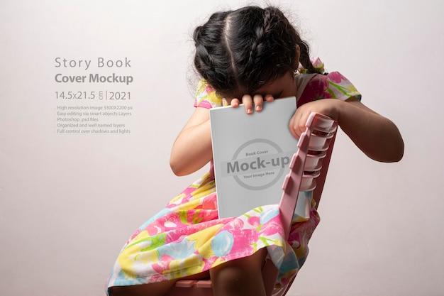 Verlegen meisje verbergt haar hoofd achter een verhalenboek