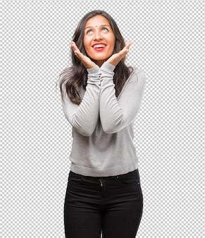 Verrast en geschokt portret van jonge indische vrouw, kijkend met brede ogen, opgewekt door een aanbieding of door een nieuwe baan, win concept