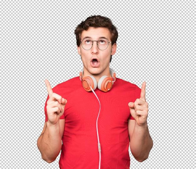 Verrast jonge man met behulp van een smartphone en wijst met zijn vinger