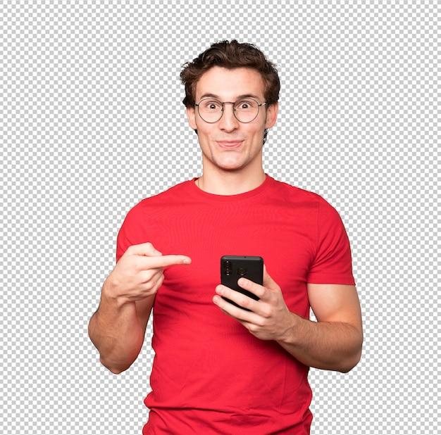 Verrast jonge man wijst en met behulp van zijn mobiele telefoon