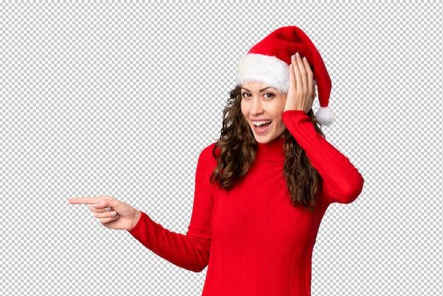 Verrast meisje met kerstmishoed en wijzende vinger aan de kant