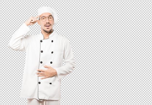 Verraste jonge chef-kok die een gebaar van concentratie doet