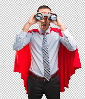 Verraste super zakenman die een verrekijker met behulp van