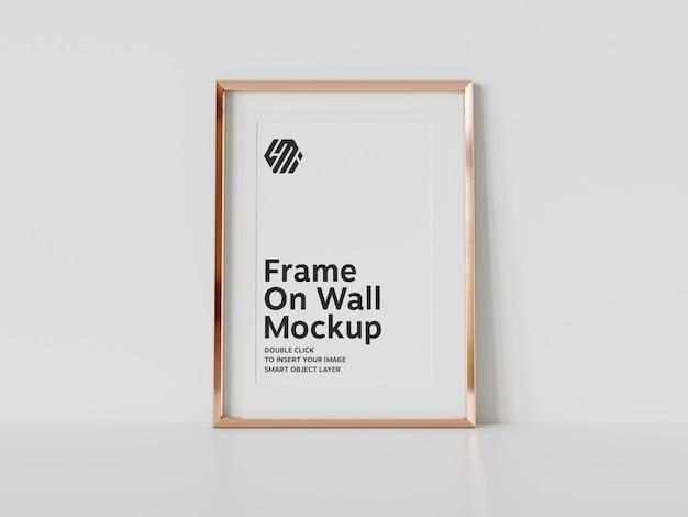 Verticaal gouden frame dat op vloermodel leunt