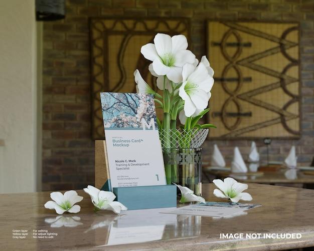 Verticale visitekaartje mockup met houten houder en bloemen