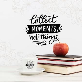 Verzamel momenten, geen dingen citaat boek met appel op stapel boeken