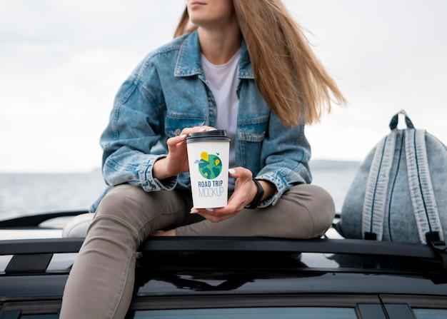 Viajero sosteniendo una taza de café de maqueta
