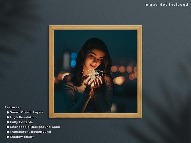 Vierkant houten fotolijstmodel dat op muurachtergrond hangt met schaduwoverlay.