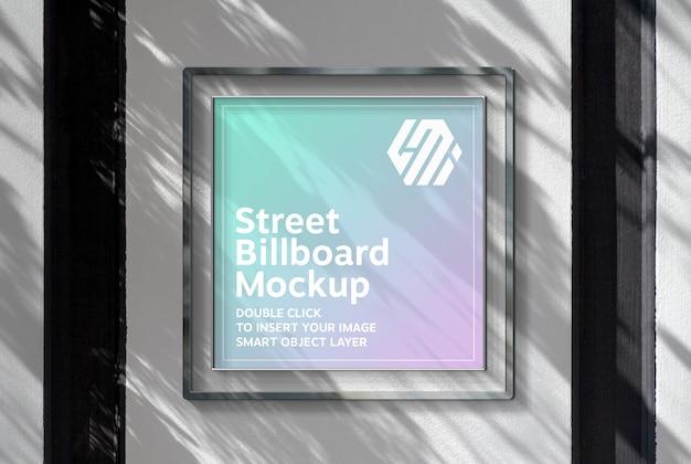 Vierkant reclamebord opknoping op zonovergoten muur mockup