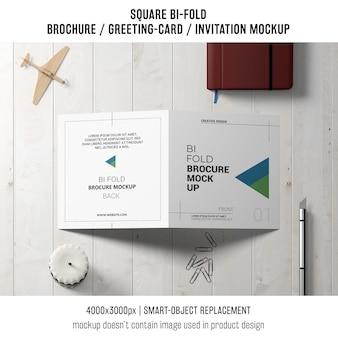 Vierkante bi-gevouwen brochure of wenskaartmodel met decoratie op tafelblad