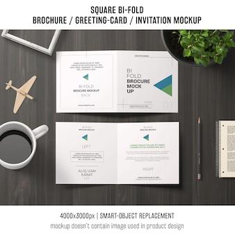 Vierkante bi-vouw brochure of wenskaart mockup op werkruimte