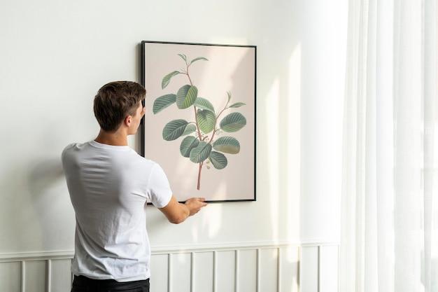 Vintage blad schilderij frame psd wordt opgehangen door een jonge man op een witte minimale muur