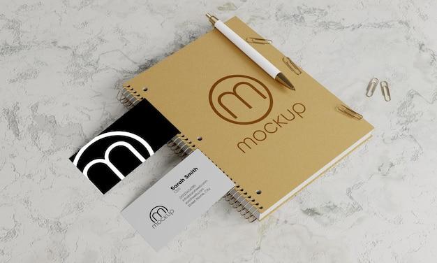 Visitekaartje en blocnote mockup met pen