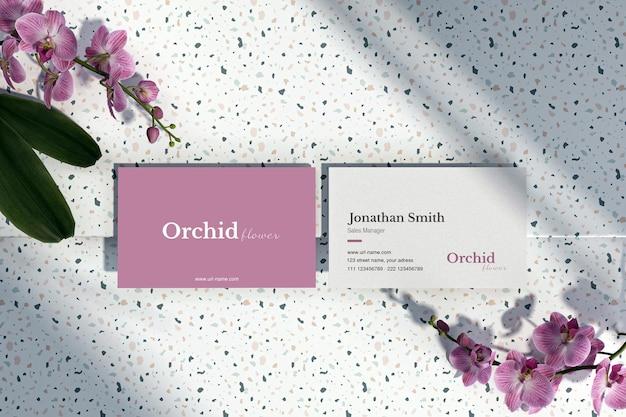 Visitekaartje met orchidee op terrazzo vloer mockup