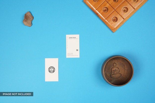 Visitekaartje mockup met boeddha kom, houten spel en steen