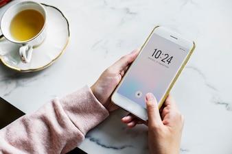 Vista aérea, de, mulher, usando, um, smartphone, e, um, xícara chá