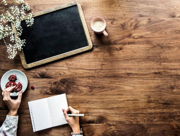 Vista aerea del bordo nero vuoto e della donna che scrive su un giornale vuoto con lo spazio della copia