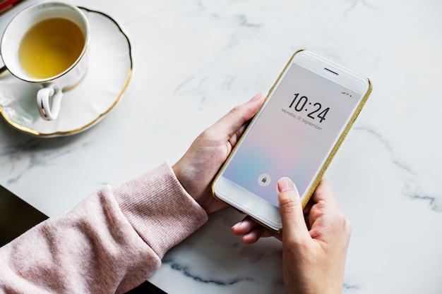 Vista aérea de mujer usando un teléfono inteligente y una taza de té