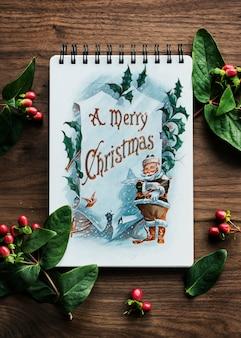 Vista aérea de la tarjeta de navidad en mesa de madera