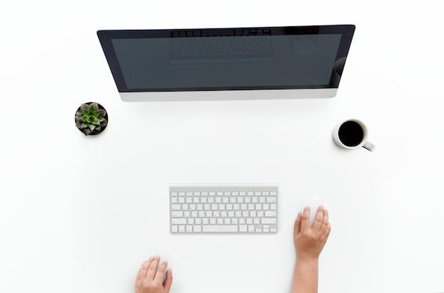 Vista de ariel de las manos usando una computadora de escritorio