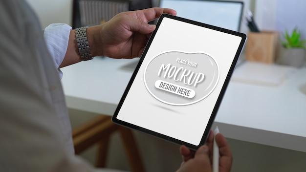 Vista de cerca del empresario sosteniendo tableta digital de maqueta y lápiz óptico