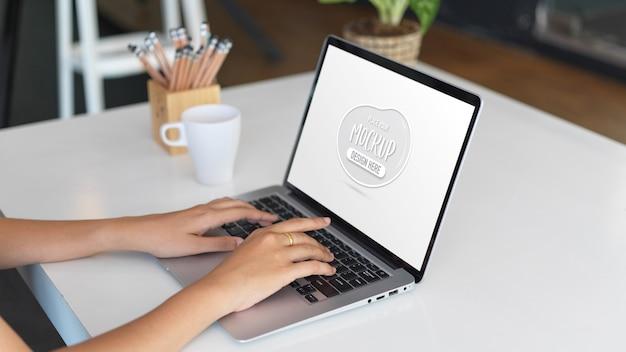 Vista de cerca de la joven empresaria escribiendo en maqueta de portátil