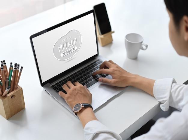 Vista de cerca del joven empresario escribiendo en maqueta de portátil