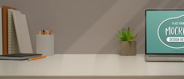 Vista de cerca de la mesa de estudio con espacio de copia y maqueta de portátil