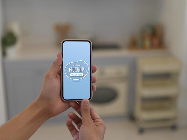 Vista cercana de manos sosteniendo smartphone maqueta