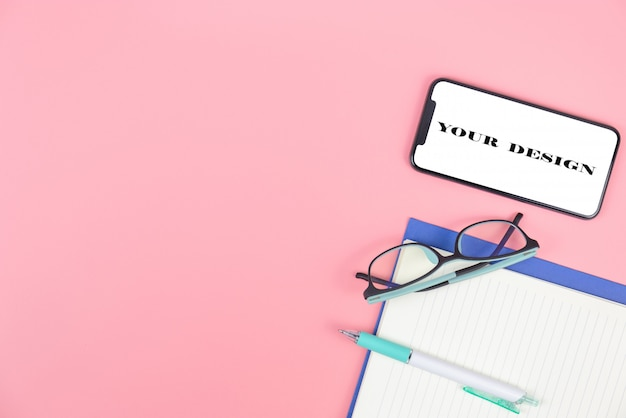 Vista dall'alto con lo spazio della copia dei vetri del libro dello smartphone e la penna al di sopra su fondo pastello rosa, disposizione piana e derisione su