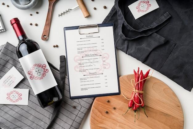 Vista dall'alto del menu con bottiglia di vino e peperoncino