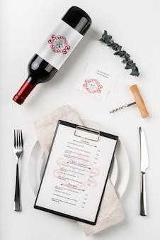 Vista dall'alto del menu con bottiglia di vino e posate