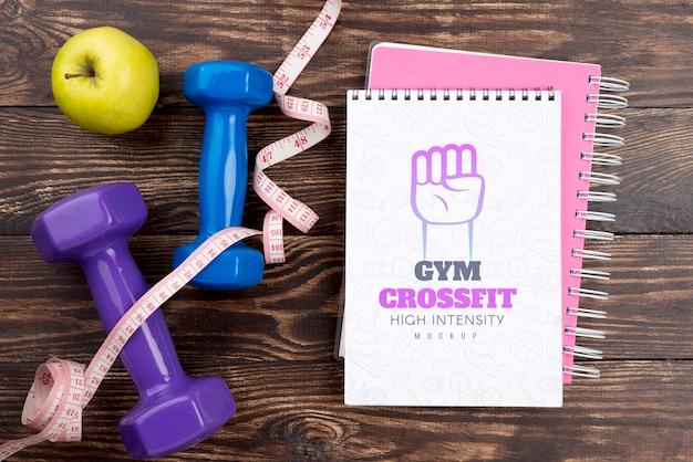 Vista dall'alto del notebook fitness con mela e pesi