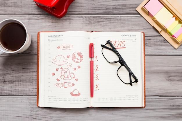 Vista dall'alto dell'agenda con occhiali e penna