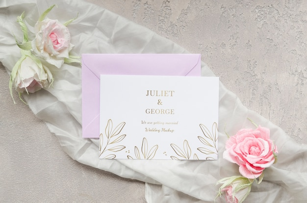 Vista dall'alto della partecipazione di nozze con rose e tessuti