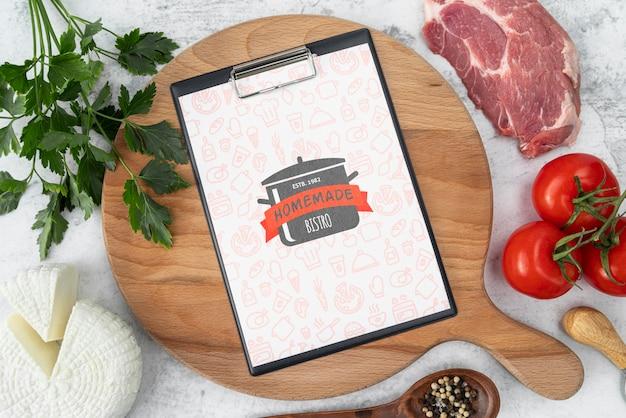 Vista dall'alto di carne con menu e pomodori