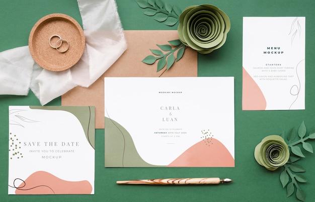 Vista dall'alto di partecipazioni di nozze con rose di carta e penna