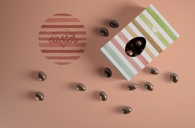 Vista dall'alto uovo di cioccolato in scatola con caramelle accanto