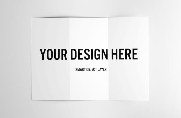 Vista de un folleto tríptico sobre maqueta de mesa blanca