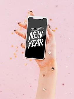 Vista frontal año nuevo letras minimalistas en el teléfono