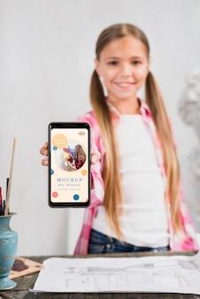 Vista frontal de la artista chica sosteniendo smartphone