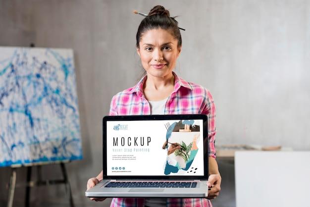 Vista frontal de la artista femenina sosteniendo el portátil