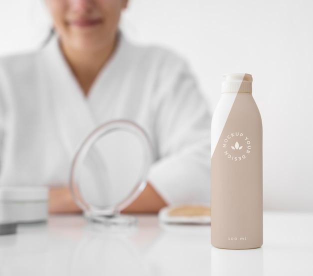 Vista frontal de la botella de crema hidratante sobre la mesa con mujer desenfocada